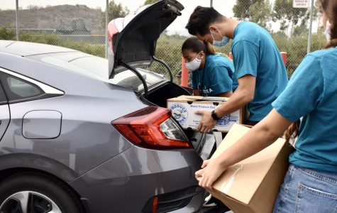 Feed Brea volunteers place groceries into a trunk during Saturday's Pop-Up Pantry event. Organizations from throughout the city coordinated to feed 871 families.