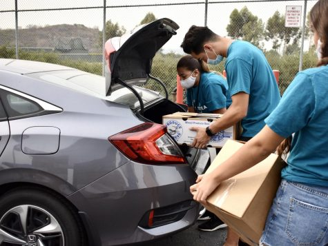 Feed Brea volunteers place groceries into a trunk during Saturday