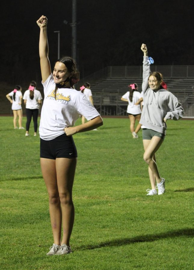 Emma Hidalgo, senior, and Peyton Lustyk, sophomore, practice a cheer during an Oct. 19 practice.