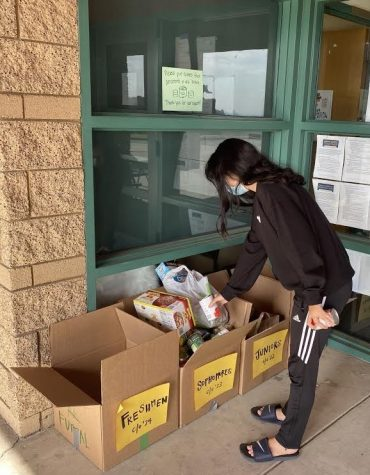 Claire Seo, sophomore, donates cans to her designated class box in front of the BOHS office. The sophomore class collected a total of 1,500 cans, the most out of all the classes.