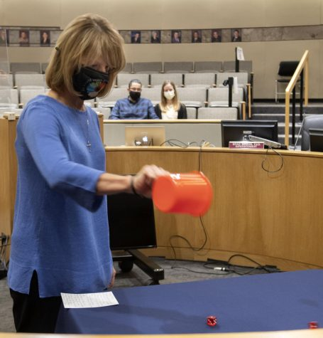 Gail Lyons, BOUSD school board member, rolls a pair of dice to determine the winner of the deadlocked Trustee Area 5 race, as Dr. Brad Mason, superintendent, and candidate Lauren Barnes (