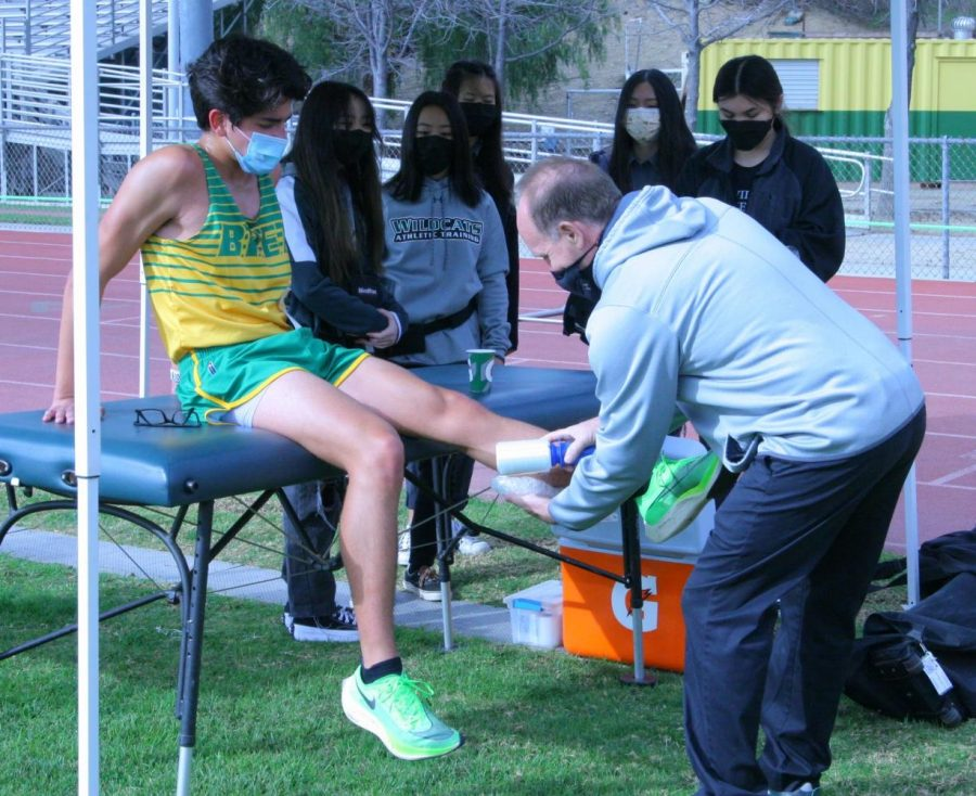 Ken McCall, athletic trainer, treats cross country runner Michael Galentine, sophomore, as athletic training student aides look on. As athletic trainer, McCall is responsible for the safety of all athletes at BOHS.