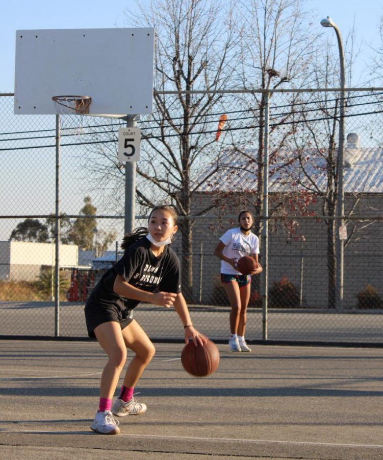 Brooklyn Kame, sophomore, and Sophia Williams, junior, practice a dribbling drill at Brea Junior High School Feb. 4. The Ladycats have since moved to the gym as COVID-19 restrictions have eased and competition resumes.