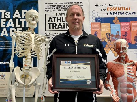 Ken McCall, athletic trainer, holds his award for North Orange County ROP Teacher of the Year. In order to be considered for this honor, teachers must be nominated by the NOCROP administration, based on demonstrating certain qualities including empowering teaching abilities, professionalism, and excellence in promoting leadership beyond the regular job obligations.