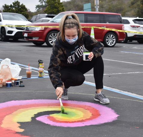 Macy Pease, senior, paints her parking spot to celebrate the last few weeks of high school. As a new BOHS tradition, seniors gathered on April 24 to paint parking spots with their desired patterns.
