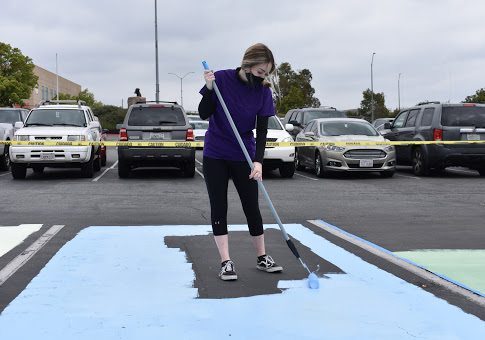 Giselle RifenBurg, senior, paints the base layer of her parking spot. After painting their own parking spots, seniors are able to park on their painted patterns whenever they come to school.