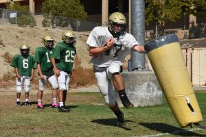 Brock LaBelle, senior, maneuvers around a tackling dummy at an Aug. 25 practice as teammates look on. Varsitys season opener was canceled this week due to COVID-19 protocols affecting Sonora High Schools ability to hold the required number of practices to compete.