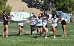 Irene Kim, junior, and her varsity golf teammates, burst through a banner at the Aug. 27 Olympics-themed rally. The rally marked the first time in two years that BOHS held an in-person, full student body event.
