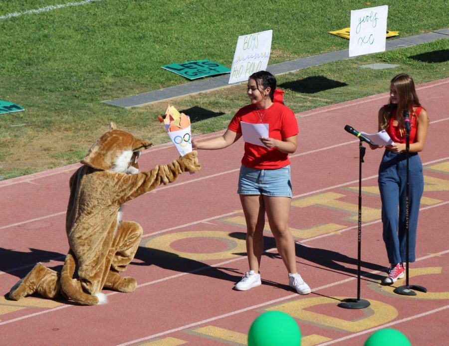 The Wildcat hands an Olympics-style torch to Nina Corral and Gracie Johnson, seniors, to mark the end of the Aug. 27 rally. The sports theme was inspired by last summers Olympics held in Tokyo.