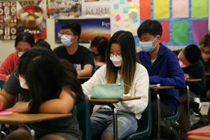"""Sophomores in Sera Yoon's Korean 2 class work on a """"Get to Know Me"""" worksheet. Students returned to complete in-person learning on Monday while following COVID-19 safety guidelines, including mandatory mask wearing."""