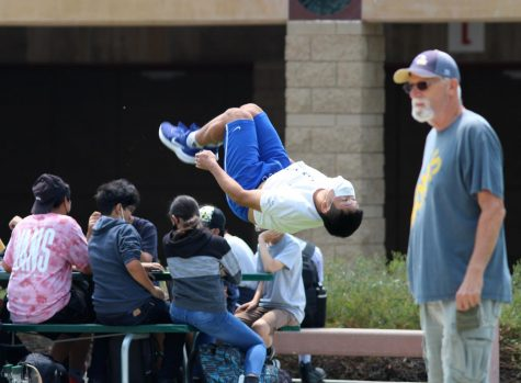 Ocean Park, freshman, performs back flips in the quad as staff member Kevin ODea observes the lunchtime crowds. The week of Aug. 16 to Aug. 20 marked the first time in 17 months that the entire student body had access to the quad for lunch.