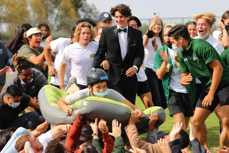 Science teacher Kurtis Chan rides a wave of seniors as Garrett Brookman, senior, and members of the senior class, cheer him on during a class versus class race at the Sept. 17 Homecoming rally.