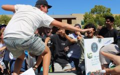 Brad Boschman, senior, rides a wave as students gather around the Surf Club table during Club Rush on Sept. 22. The multi-day event, hosted by ASB, featured presentations by 74 campus clubs.